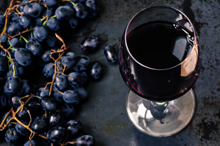 Wijnglas van rode wijn met druiven op een zwarte achtergrond Stockfoto
