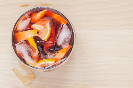 lemon: Sangria wine in the wineglass and pieces of ice on wooden table