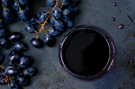 pinot: Red wine in a wineglass and black grape top view