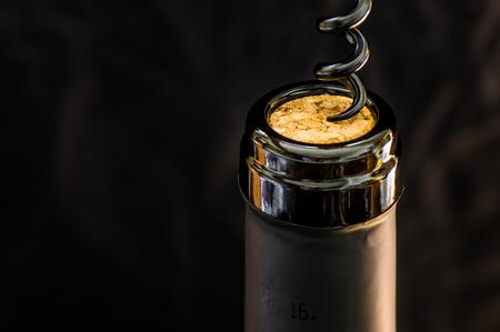 uncork: Opening a bottle of wine corkscrew closeup