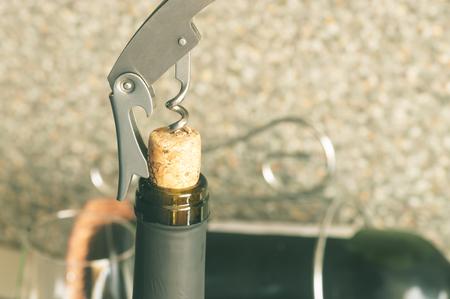 uncork: Steel corkscrew opens a bottle of wine closeup Stock Photo