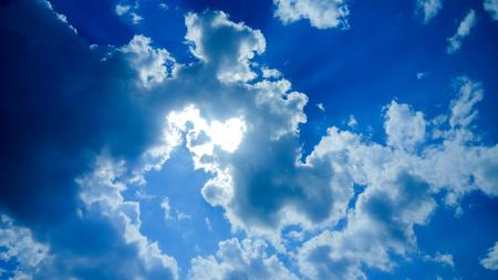 太陽は明るい青空に雲の陰に隠れた、太陽の光線が雲の切れ間からの道を作る