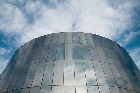 Glass round building with cloudy sky reflecting. Stock Photo