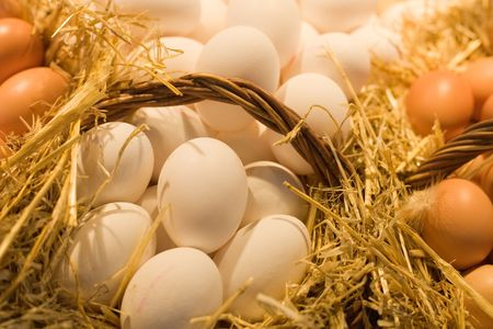 Fresh white and brown eggs in straw baskets.
