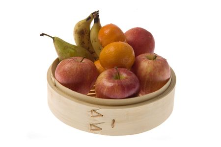 Bamboo steamer with apples, pears, tangerines and bananas,. photo