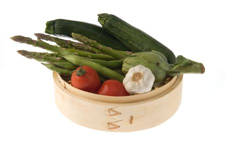Bamboo steamer with tomatoes, asparagus, courgettes, bean pods and a head of garlic. photo