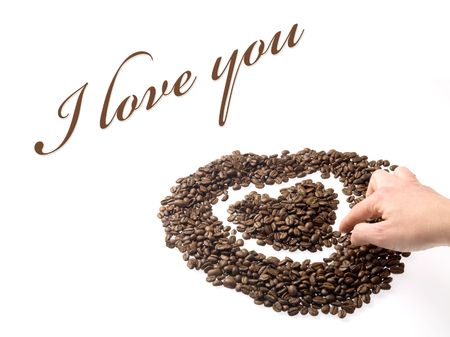 Hand designing a heart with coffee beans, as a symbol of love.