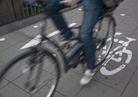 Speedy cyclist commuting on an urban cycleway. Stock Photo