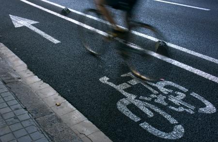 cycleway: Speedy ciclista pendolarismo su una pista ciclabile urbana.