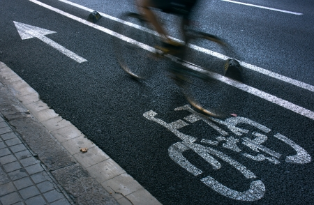 cycleway: Speedy cyclist commuting on an urban cycleway. Stock Photo