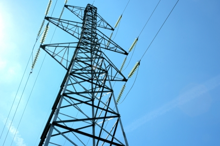 An electricity power tower against a blue sky photo