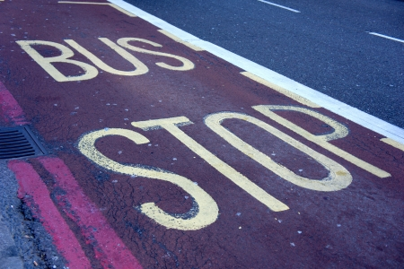 Bus stop sign painted on red bus lane photo