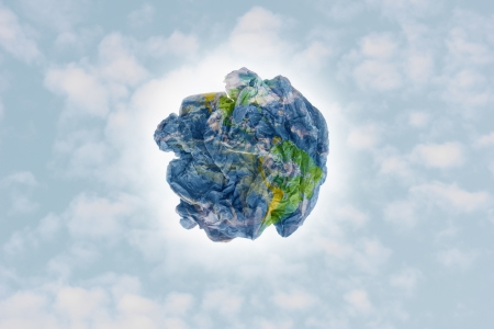 Planet paper trash over a cloudy sky background as a metaphor for environmental issues and concepts. photo