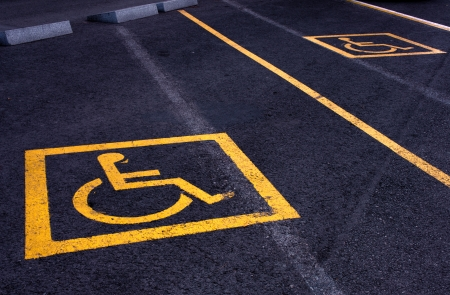 Yellow signs of parking areas reserved for disabled people. photo