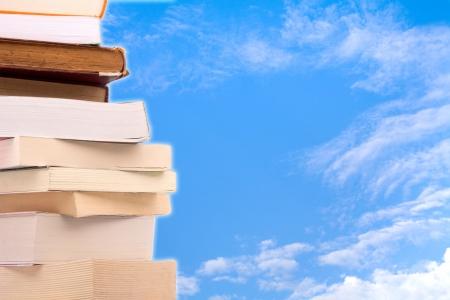 Old books in a stack with sky background photo