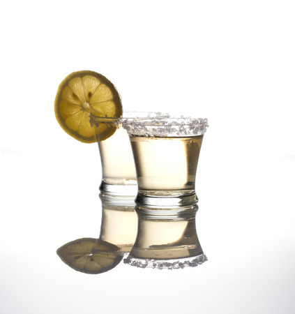 Two shots of tequila on white with reflections Stock Photo