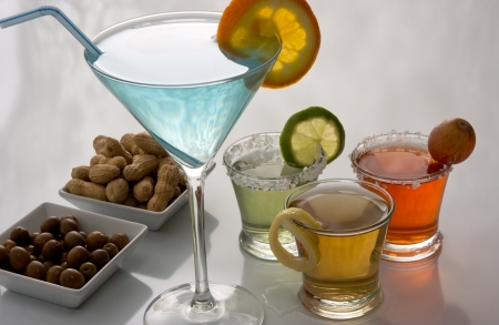 Colorful alcoholic cocktails with olives and peanuts snacks  photo