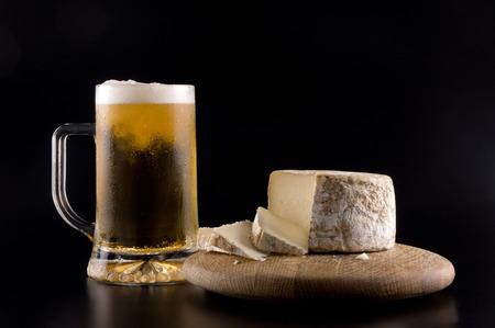 queso de cabra: Una cerveza fr�a chuleta de hielo con una rueda de queso en una tabla de madera