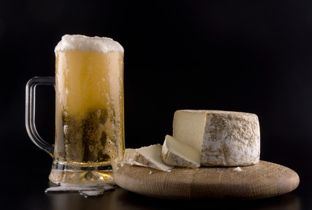 Frosted glass overflowing beer and cured goat cheese over black background