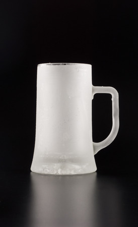 An empty and frozen glass tankard over black background Stock Photo