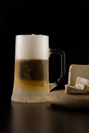 jarra de cerveza: Una jarra de cerveza fr�a y queso de cabra sobre fondo negro Foto de archivo