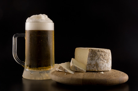 Foaming beer with artisanal goat cheese on wooden board Stock Photo