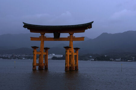 Floating torii gate in Miyajima (shrine island, in Japanese), in front of Hiroshima, Japan. Torii gates mark the approach and entrance to a Shinto shrine. Editorial