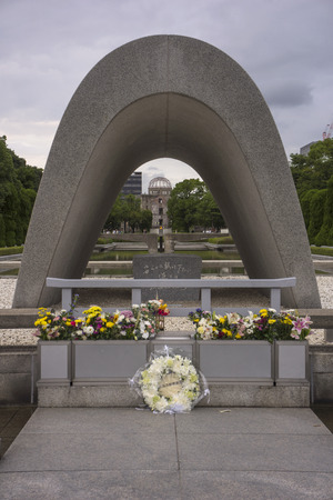 Hiroshima, Japan - August 18, 2014: Visitors in the Peace Memorial Park in Hiroshima, which is dedicated to the legacy of Hiroshima as the first city in the world to suffer a nuclear attack. The Atomic Dome can be seen thought the cenotaph.