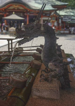 Source of water in the shape of a dragon for the ritual of washing hands in the entrance to a Shinto temple in Japan. Stock Photo