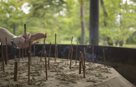 spiritually: A person placing a stick in a japanese burnining incense worship site