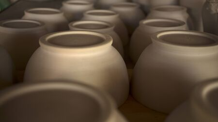 Group of round ceramic pots waiting to be baked. Shallow focus.