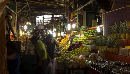 Cuernavaca, Mexico - Dec 22, 2012: Customers buying food before Christmas and dependents attending the stalls of a big fresh food market . Editorial