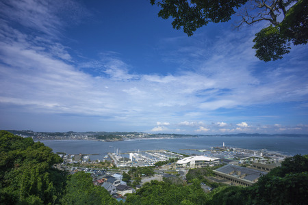 Enoshima, Japan - August 8, 2014 Panorama view of The Sagami Bay of Kanawaga Prefecture. On the front, the port of Enoshima island and on the background, the city of Fujisawa, home to some of the closest sandy beaches to Tokyo.