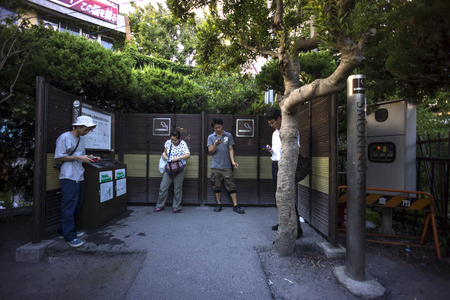 Tokio, Japan August 8, 2014: Smokers at a public smoking spot. Smoking facilities  have been set up in several areas as a result of the antismoking trend in Japan.