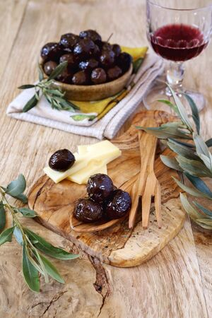 mediterranean cuisine: Mediterranean cuisine: marinated olives, slices of cheese and glass of red wine