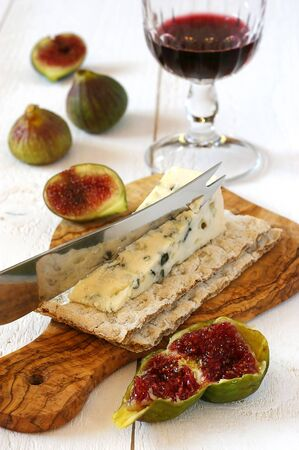 sappy: French mould cheese, glass of red wine and ripe figs on cutting board from olive wood