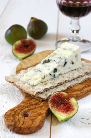 compatibility: French mould cheese, glass of red wine and ripe figs on cutting board from olive wood