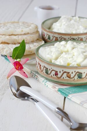 dietetical: Diet breakfast: crispbread, cottage cheese in ceramic ware hand-painted and fuchsia flower Stock Photo