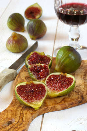sappy: Glass of red wine and ripe figs on cutting board from olive wood Stock Photo
