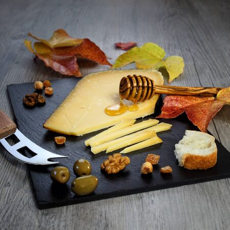 collation: Solid cheeses plate: Dutch Gouda cheese, olives provencal, walnuts and autumn leaves