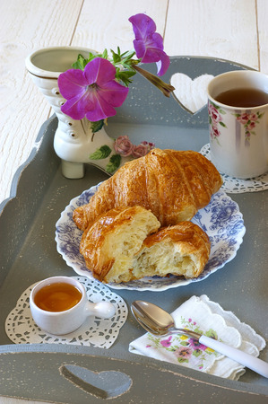blanche: French breakfast in neo-provencal style with flowers on gray tea tray and croissant