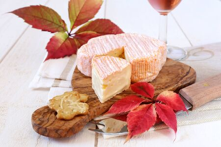 rose wine: Autumn still life: red leaves, French cheese, crackers and a glass of rose wine