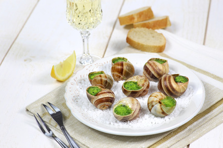 Escargots, traditional French dish: snails sauce Burgundy and a glass of white wine Archivio Fotografico