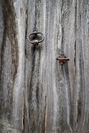 crannied: Texture: fragment of an old wooden door with hardware elements Stock Photo