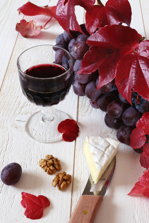 morsel: French cheese Coulommiers, glass of red wine, walnuts, bunch of red grapes and autumn leaves