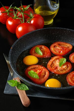 hearty: Hearty breakfast, cooking: fried eggs with tomatoes, basil and olive oil Stock Photo