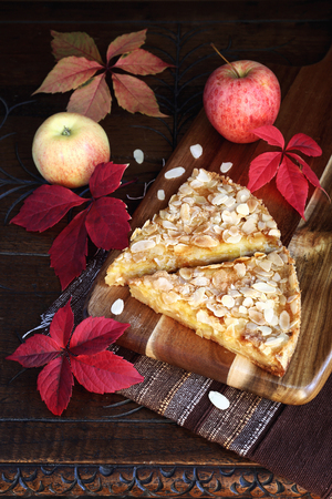 morsel: Autumn still life: apple tart, colorful leaves on an old wooden table