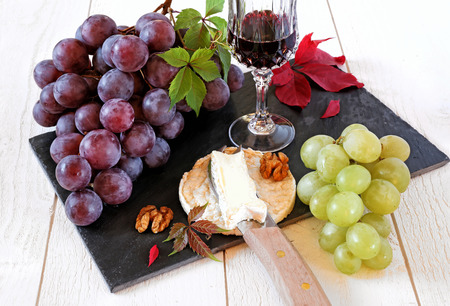still lifes: Autumn fruit-piece: red and green grapes, French cheese, walnuts and glass of burgundy