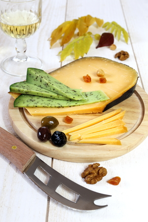 collation: Cheese platter: solid cheese, Provencal olives and wineglass Stock Photo