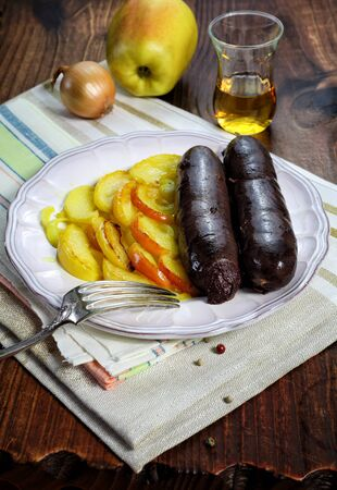 french cuisine: Traditional French cuisine: Blood sausage, apples, onion and Calvados Stock Photo